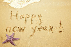 Happy new year  on sand. Happy new year  Written in Sand on Beach and a Starfish Stock Image
