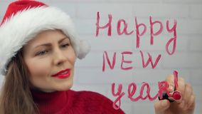 Happy New Year. Santa girl writes lipstick on glass words happy new year. Beautiful girl in hat sending a message. Stock Photography