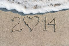 Happy New Year 2014 on the sea sandy beach with heart Stock Image