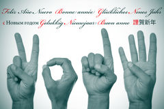 Happy new year 2014. Sentence happy new year written in different languages, such as spanish, french, german, russian, dutch, italian and japanese, and hands Stock Photography