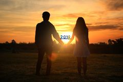 Happy new year 2018 ,Shadow image of couples holding hands with. The morning light.Hand in hand together,selective focus with Lens Flare,silhouette stock photography