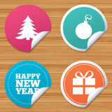 Happy new year sign. Christmas tree and gift box. Round stickers or website banners. Happy new year icon. Christmas tree and gift box sign symbols. Circle Royalty Free Stock Image