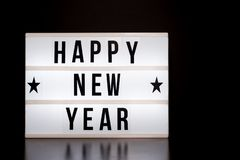 Happy New Year sign - cinema style lettering on light box & black background. Minimal stock images