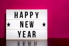 Happy New Year sign - cinema style lettering on light box & hot pink background. Happy New Year sign - cinema style lettering on light box stock photo