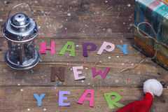 Happy New Year sign of colored letters. Happy New Year, the word on the old wooden background of colored letters Royalty Free Stock Images