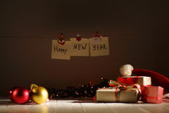 The Happy New Year sign is hanging on the rope with the help of Christmas foldings behind the presents, glowing garlands. And baubles stock photo