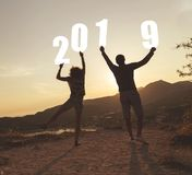 Happy New 2019 Year. Silhouette of a couple in love standing near a seaside cliff, holding numbers 2019 and looking at a beautiful sunset at Valtos beach in stock images