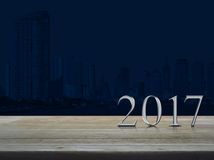 Happy new year 2017 silver metal text on wooden table over city Stock Photos