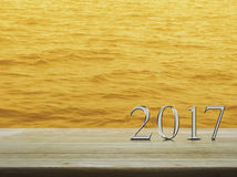Happy new year 2017 silver metal text on wooden table over sea Stock Photos