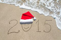 Happy new year 2015 with smiley face in santa hat on sandy beach. With wave - christmas holiday concept Royalty Free Stock Photo