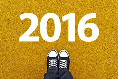 Happy New Year 2016 with Sneakers from Above. Happy New Year 2016 with Person Wearing Black Sneakers from Above, Top View Royalty Free Stock Photo