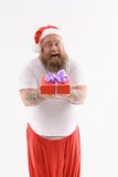 Happy New Year. This special gift is for you. Joyful fat Santa Claus is showing box to camera. He is standing and laughing. Isolated Royalty Free Stock Image