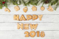 Happy New Year 2018. Table top shot of gingerbread cookies shaped as letters Happy New 2018 with some fir branches, pine cones and christmas tree ornaments Royalty Free Stock Photo