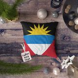 Happy New Year tag with Antigua and Barbuda flag on pillow. Christmas decoration concept on wooden table with lovely objects.  royalty free stock photos