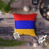 Happy New Year tag with Armenia flag on pillow. Christmas decoration concept on wooden table with lovely objects stock images