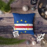 Happy New Year tag with Cape Verde Islands flag on pillow. Christmas decoration concept on wooden table with lovely objects stock images