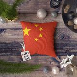Happy New Year tag with China flag on pillow. Christmas decoration concept on wooden table with lovely objects stock photo