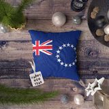 Happy New Year tag with Cook Islands flag on pillow. Christmas decoration concept on wooden table with lovely objects stock photography