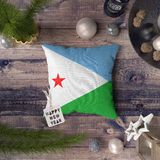 Happy New Year tag with Djibouti flag on pillow. Christmas decoration concept on wooden table with lovely objects.  stock images