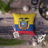 Happy New Year tag with Ecuador flag on pillow. Christmas decoration concept on wooden table with lovely objects stock photo