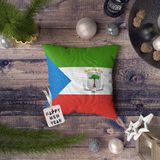 Happy New Year tag with Equatorial Guinea flag on pillow. Christmas decoration concept on wooden table with lovely objects.  royalty free stock images