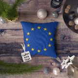 Happy New Year tag with European Union flag on pillow. Christmas decoration concept on wooden table with lovely objects royalty free stock photos