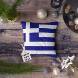 Happy New Year tag with Greece flag on pillow. Christmas decoration concept on wooden table with lovely objects stock photography