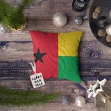 Happy New Year tag with Guinea Bissau flag on pillow. Christmas decoration concept on wooden table with lovely objects.  royalty free stock image