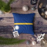 Happy New Year tag with Nauru flag on pillow. Christmas decoration concept on wooden table with lovely objects stock image