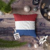 Happy New Year tag with Netherlands flag on pillow. Christmas decoration concept on wooden table with lovely objects stock photos