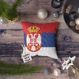 Happy New Year tag with Serbia flag on pillow. Christmas decoration concept on wooden table with lovely objects royalty free stock photography