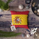 Happy New Year tag with Spain flag on pillow. Christmas decoration concept on wooden table with lovely objects stock photography