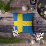 Happy New Year tag with Sweden flag on pillow. Christmas decoration concept on wooden table with lovely objects stock image