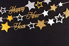 Happy New Year text banner with strings of stars against black stock image