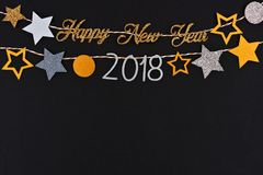 Happy New Year 2018 text banner with strings of stars against black. Happy New Year 2018 glitter text banner with strings of gold and silver stars against a Royalty Free Stock Images