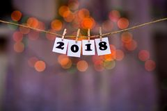 Happy new year 2018 text on papers with clothespins with garland bokeh on background Royalty Free Stock Images