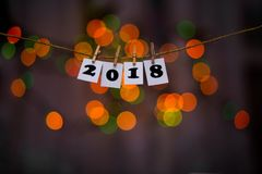 Happy new year 2018 text on papers with clothespins with garland bokeh on background Stock Images