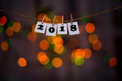 Happy new year 2018 text on papers with clothespins with garland bokeh on background Royalty Free Stock Photography