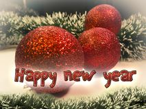Happy New Year text in red color on christmas tree ball toys and garlands background. Stock Photography