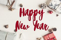 Happy new year text, seasonal greetings card sign. stylish wrapp. Ed present boxes with ornaments on white wooden background top view, christmas flat lay Royalty Free Stock Photos