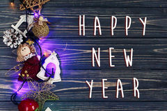 Happy new year text sign on christmas garland lights border ang Royalty Free Stock Images