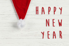 Happy new year text sign on christmas santa hat on white rustic. Wooden background. space for text. holiday greeting card concept. unusual creative view Royalty Free Stock Photos