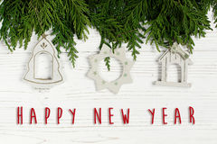 Happy new year text sign on christmas simple toys on green tree. Branches on stylish white rustic wooden background. space for. holiday greeting card concept royalty free stock photo