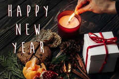 Happy new year text sign on hand lighting up candle and present Royalty Free Stock Photo