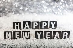 Happy new year text on snow, abstract bokeh lights background. Copy space stock photos