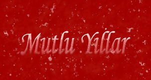 Happy New Year text in Turkish Mutlu Yillar turns to dust from. Bottom on red background Stock Image