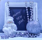 Happy New Year text in a white wooden frame with a snowman, silv. Er ball and beads Royalty Free Stock Photography