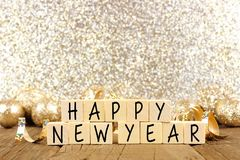 Happy New Year text on wooden blocks with golden background stock photos