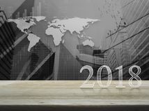 Happy new year 2018 text on wooden table. Over world map with financial graph and city tower, Elements of this image furnished by NASA Stock Images