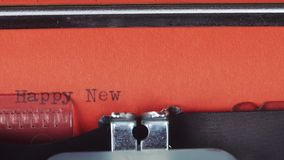 Happy New Year - Typed on a old vintage typewriter. Printed on red paper. The red paper is inserted into the typewriter.  stock footage